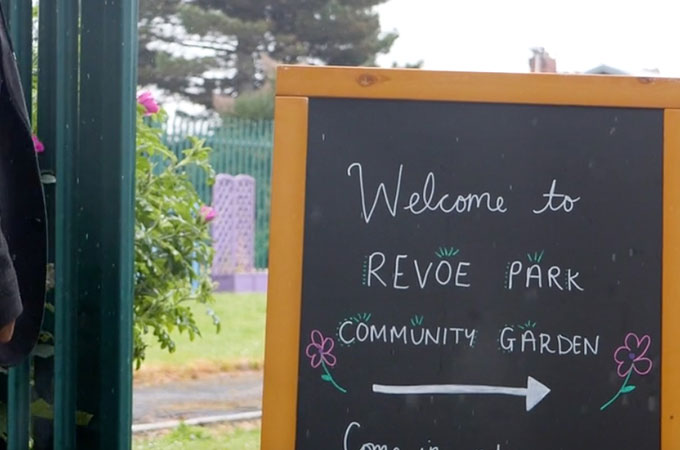 A board sign for the community garden